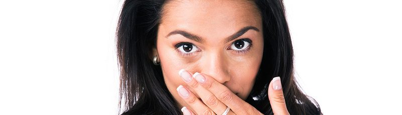 Attractive businesswoman covering her mouth with hands and looking at camera. Isolated over white ba